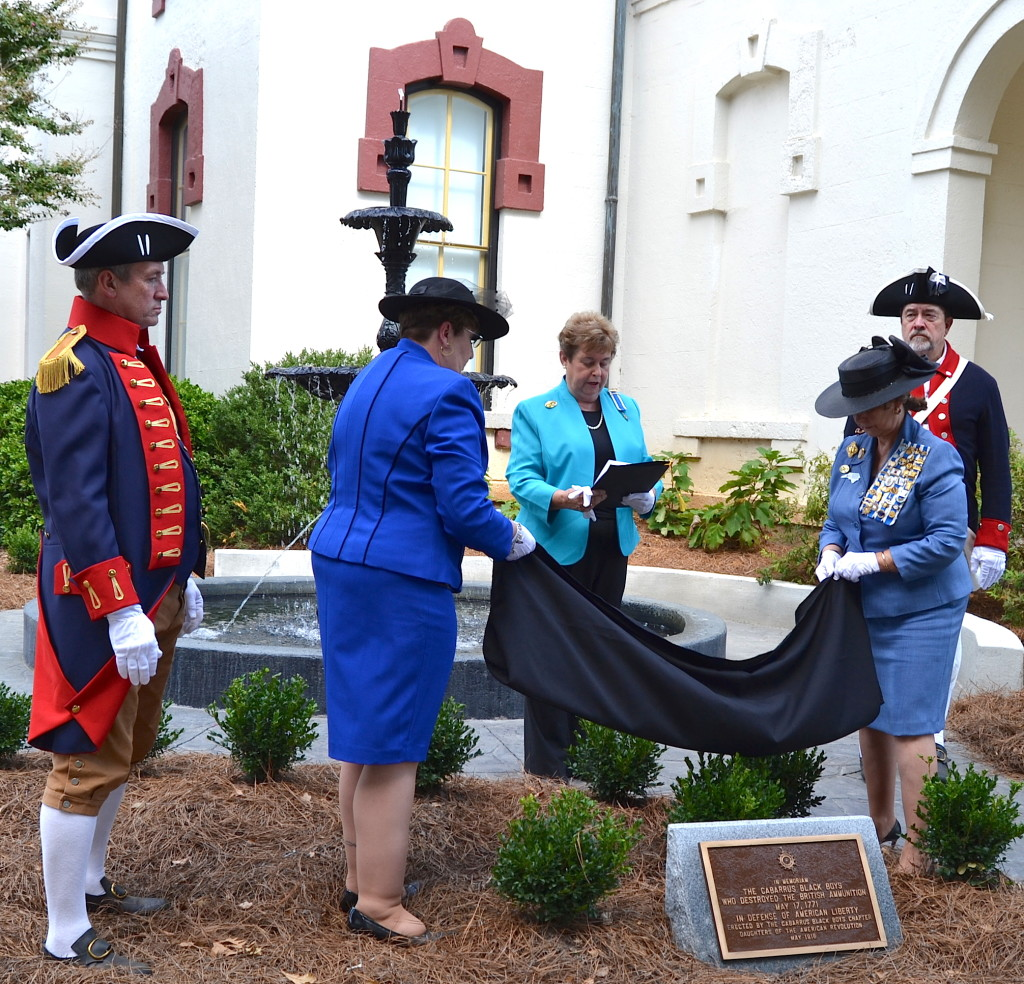 Mecklenburg SAR members Dave Alls, at left, and Ken Luckey, at right, assist Cabarrus Black Boys DAR chapter project chairs Louis Marlow and Deloris Clodfelter with the unveiling ceremony.