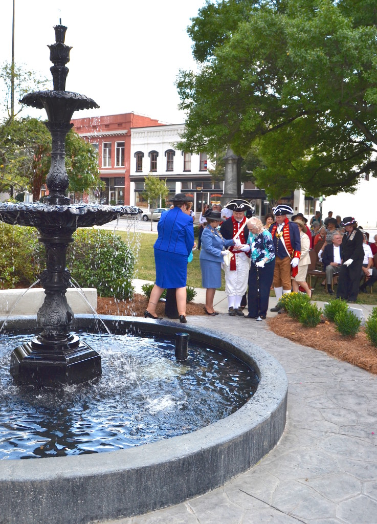 Mecklenburg SAR members Dave Alls, Ken Luckey, North Carolina SAR president Tim Berly, Jim Tatum and Jay Joyce escort DAR members to place original coins back into the fountain during the rededication ceremony.