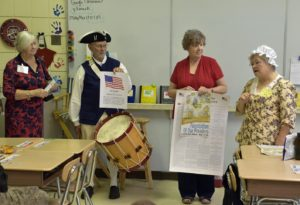 Rolf Maris, and his wife Becky, a DAR member, along with two school teachers, explain the posters to the class.